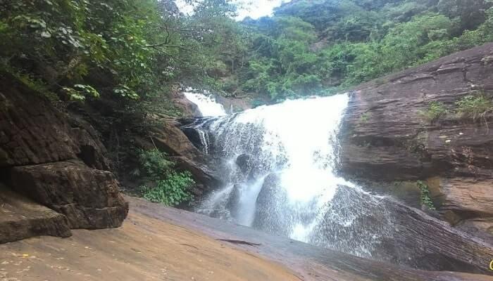 Water falling between towering rocks creating one of the Best waterfalls in Odisha
